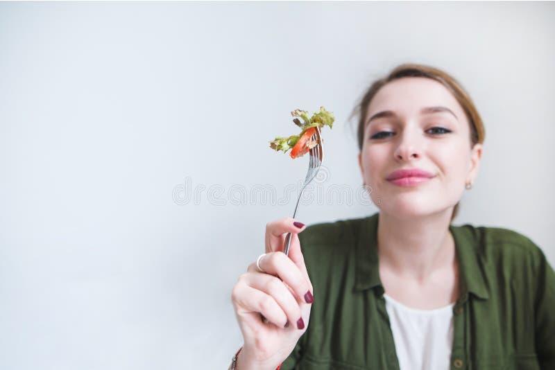 Piękna kobieta z pomidorem i zielenią na rozwidleniu w jej ręce odizolowywa na szarym tle zdjęcie royalty free