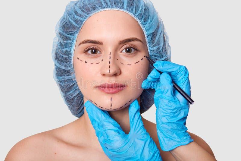 Piękna kobieta zaznaczał strzały pod oczami Dama chce ulepszać jej pojawienie Chirurg plastyczny z błękitnym rękawiczka remisów c obrazy stock
