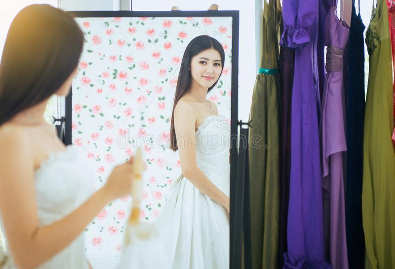 Piękna młoda azjatykcia kobiety panna młoda próbuje na ślubnej sukni przy przodem lustro, Szczęśliwy i uśmiechnięty zdjęcia royalty free