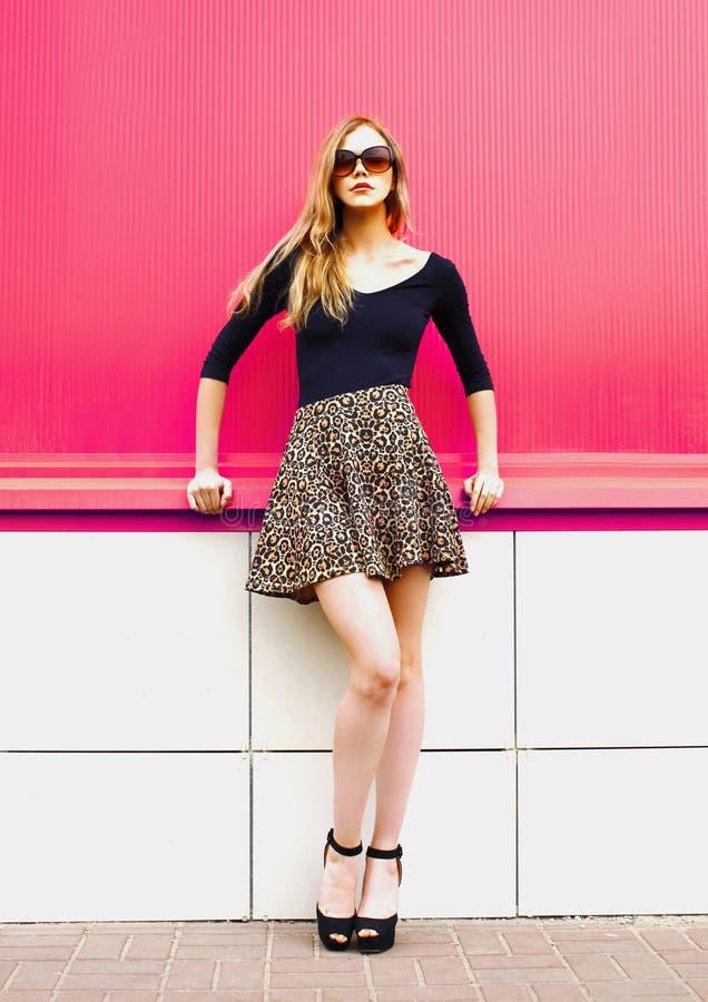 Piękna młoda blondynki kobieta pozuje w lampartów okularach przeciwsłonecznych na miasto ulicie nad kolorową menchii ścianą i spó zdjęcie royalty free