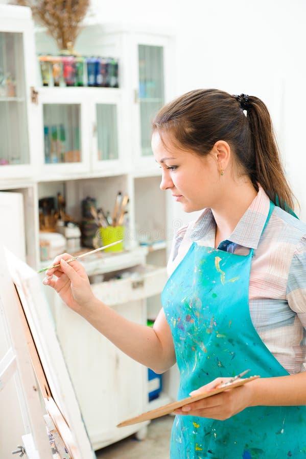 Piękna młoda dziewczyna rysuje obrazka farby na sztuki lekcji obrazy royalty free