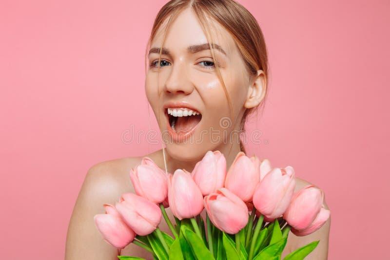 Piękna młoda dziewczyna trzyma bukiet różowi tulipany na różowym tle z czystą skórą, obraz royalty free