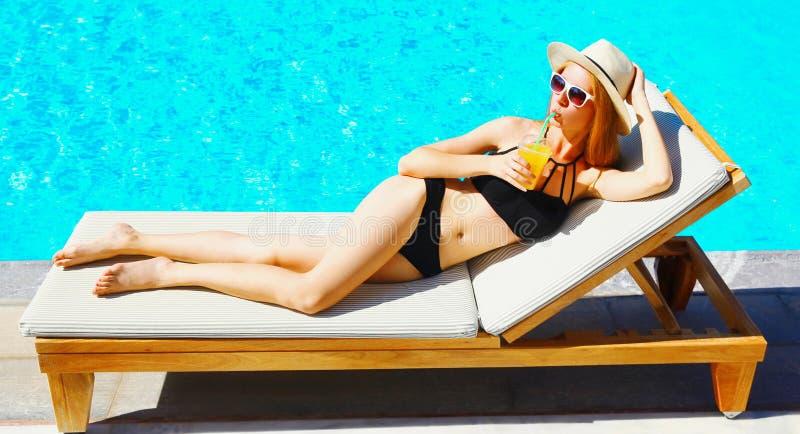 piękna młoda kobieta pije sok kłama na deckchair nad błękitne wody basenu tłem zdjęcia stock