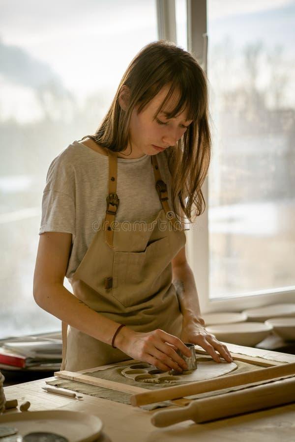 Piękna młoda kobieta robi ceramicznemu artykuły, pleśnieje kształt w miejsce pracy w słońca świetle Pojęcie dla kobiety w freelan obraz stock