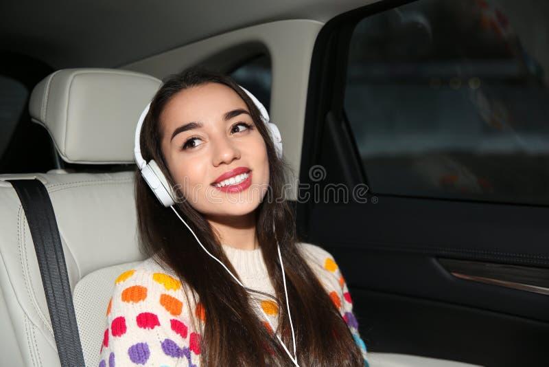 Piękna młoda kobieta słucha muzyka z hełmofonami w samochodzie fotografia stock