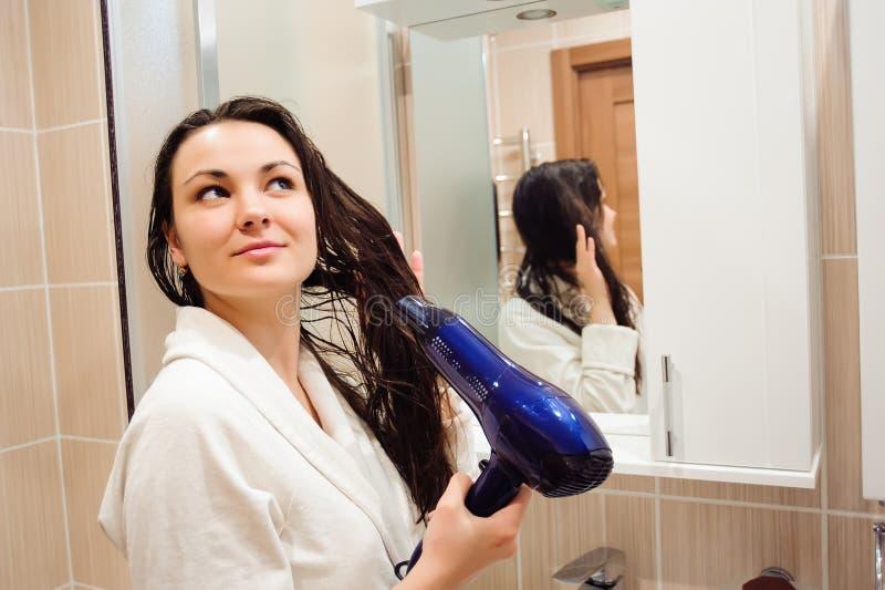 Piękna młoda kobieta w kąpielowym ręczniku używa włosianą suszarkę i ono uśmiecha się podczas gdy patrzejący w lustro w łazience obrazy stock