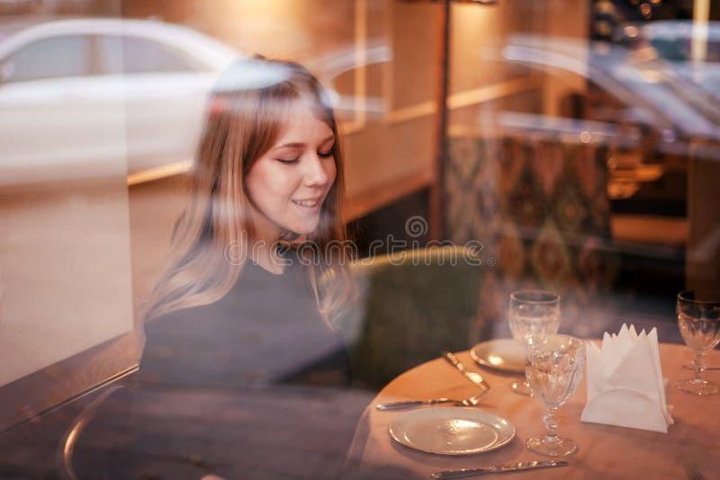 Piękna młoda uśmiechnięta i szczęśliwa kobiety blondynka przy stołem w restauracji przez szkła Odbicia obraz royalty free