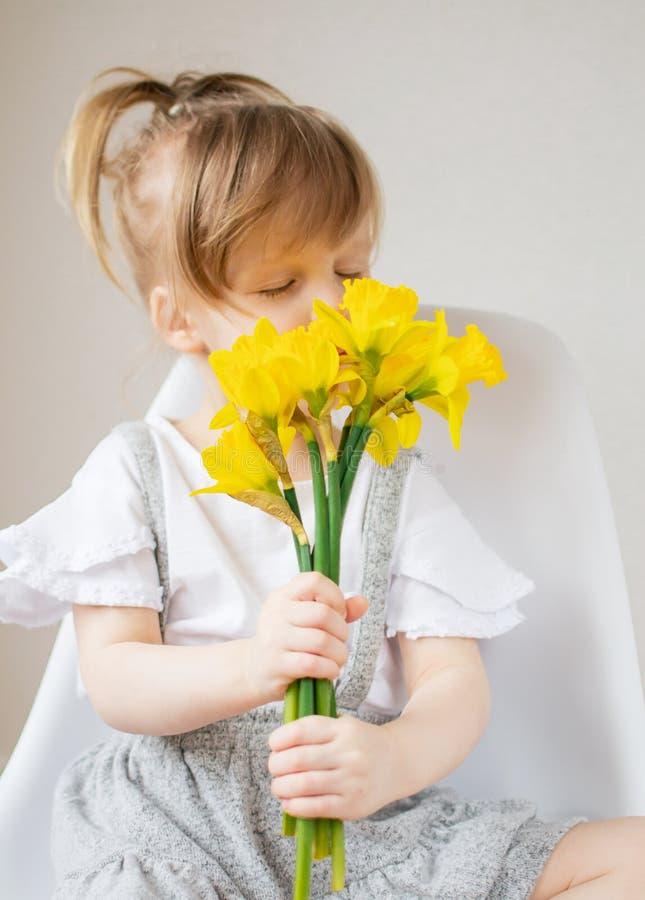 Piękna mała dziewczynka trzyma bukiet kwiaty zdjęcia royalty free