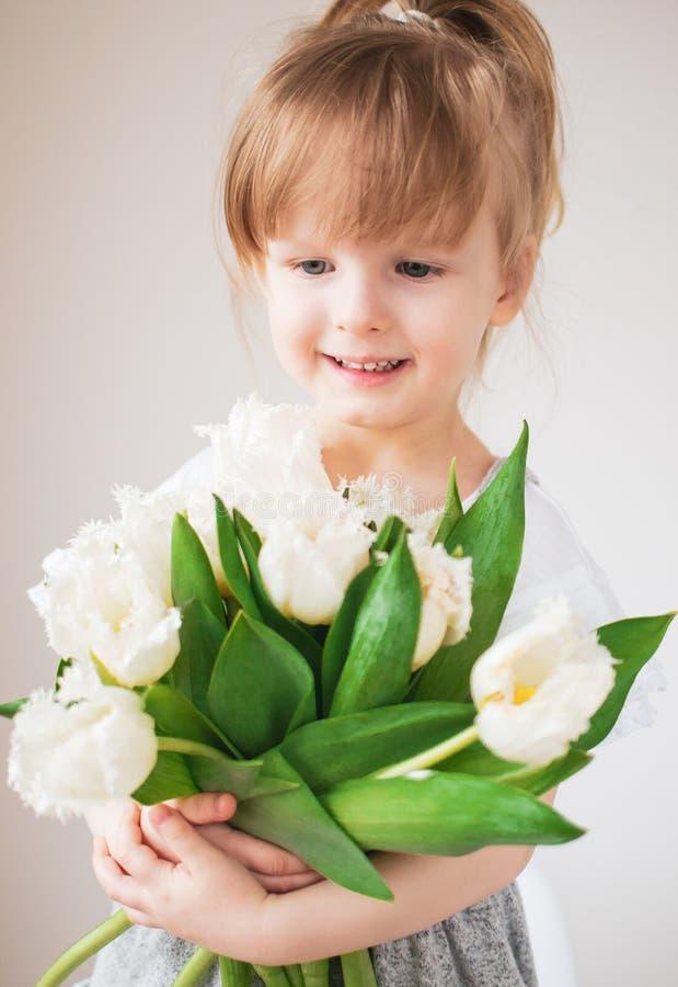 Piękna mała dziewczynka trzyma bukiet kwiaty zdjęcie royalty free