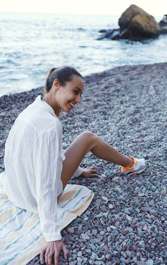 Piękna seksowna szczęśliwa kobieta ma zabawę na plaży przy kurortem Młoda uśmiechnięta kobieta w białej koszula siedzi na kamieni obrazy royalty free