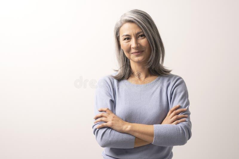 Piękna siwowłosa kobieta z krzyżować rękami fotografia royalty free