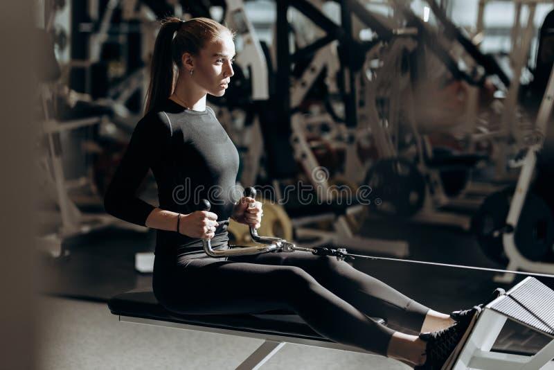 Piękna sportowa dziewczyna ubierająca ubierającą w czarnym sportswear robi sportów ćwiczeniom z wyposażeniem na ławce zdjęcia stock