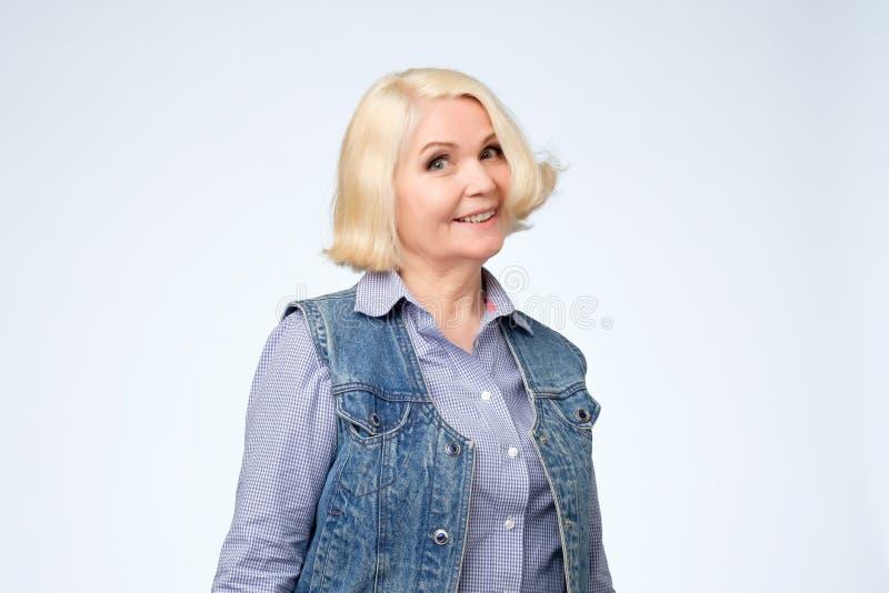 Piękna stara blondynki kobieta ono uśmiecha się i stoi zdjęcia royalty free