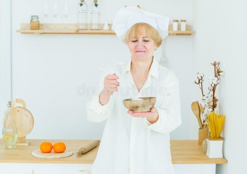 Piękna starsza kobieta w kucbarskiej nakrętce z drewnianym garnkiem w kuchni w domu fotografia royalty free