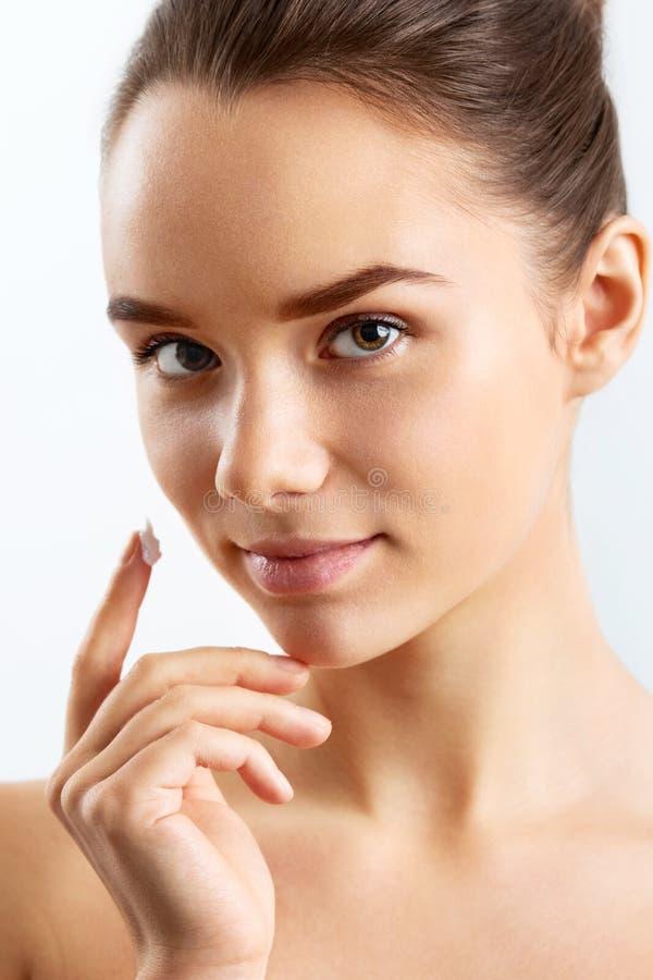 Piękna wzorcowa stosuje kosmetyczna śmietanka na jej twarzy fotografia royalty free
