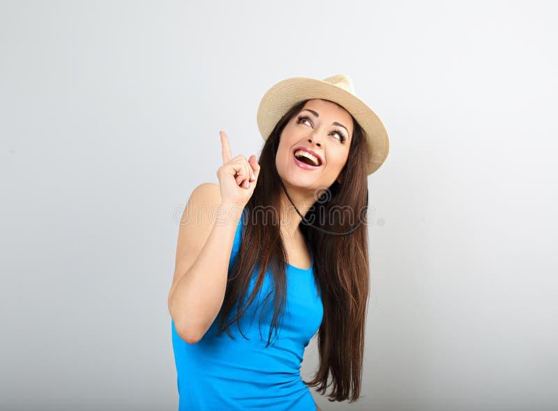 Piękna z podnieceniem przypadkowa kobieta wskazuje palec w w górę jaskrawego błękita wierzchołka z otwartym usta w lato kapeluszu obraz stock