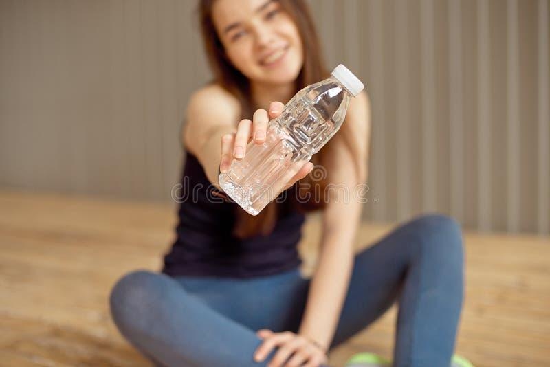 Pięknego młodego dorosłego szczęśliwego kobiety mienia plastikowa butelka z jasną wodą w ręce stoi blisko popielatej ściany i ono zdjęcia stock