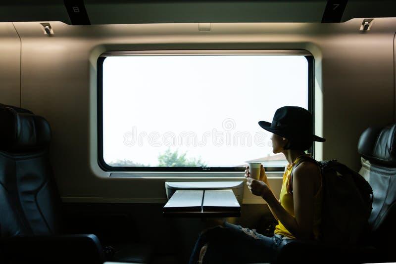 Pięknego modnisia azjatykcia kobieta podróżuje na pociągu Siedzieć na czarnym rzemiennym wygodnym wygody siedzeniu w klasie busin zdjęcie stock