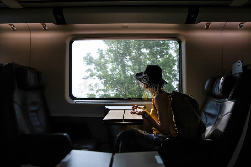 Pięknego modnisia azjatykcia kobieta podróżuje na pociągu zdjęcia stock