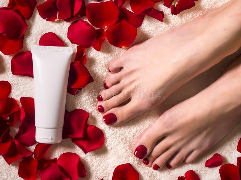 Piękni żeńscy cieki z pięknym pedicure'em z tubką śmietanka na Terry ręczniku z różanymi płatkami Zdrój i skóra obrazy royalty free
