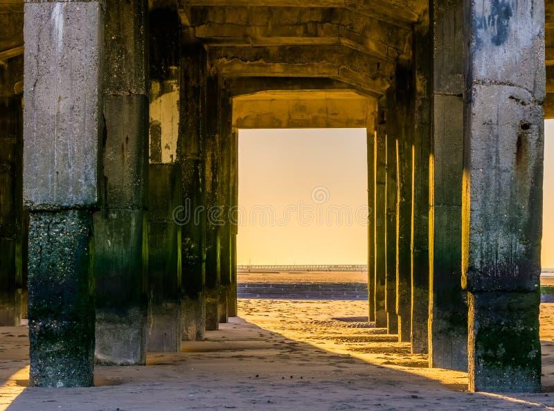 Piękni wietrzejący kamienni słupy pod jetty przy plażą, pogodną pogodą i kolorowym niebem, obraz royalty free