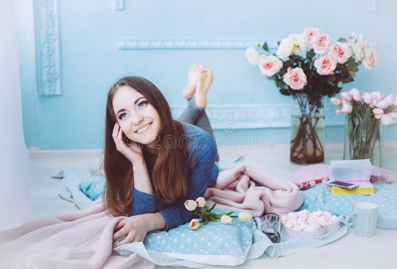 Piękny dziewczyny lying on the beach na podłodze i ono uśmiecha się, z tulipanowymi kwiatami na błękitnym ściennym tle w wiosna r obrazy royalty free