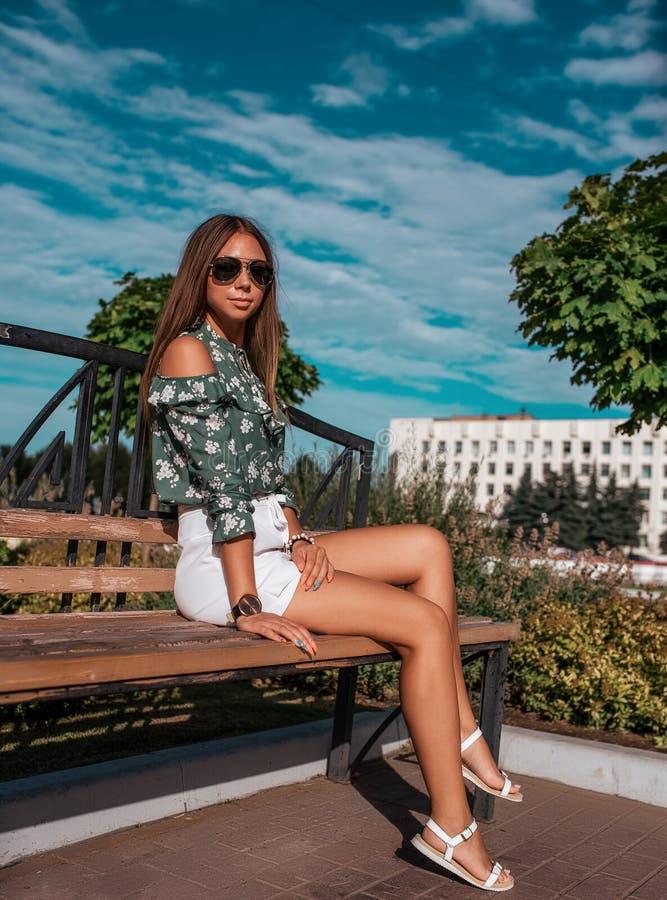 Piękny dziewczyny obsiadanie na ławce na lato ulicie w mieście W okularach przeciwsłonecznych, cieszy się odpoczynek w turystyczn fotografia stock