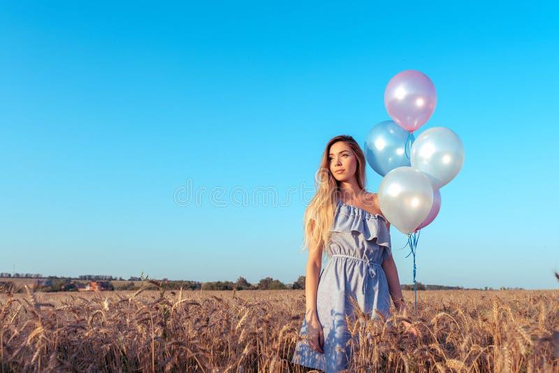 Piękny i młoda dziewczyno stoi lata pszenicznego pole W jego ręce barwiący balony Emocji calmness równowaga, zaufanie zdjęcia stock