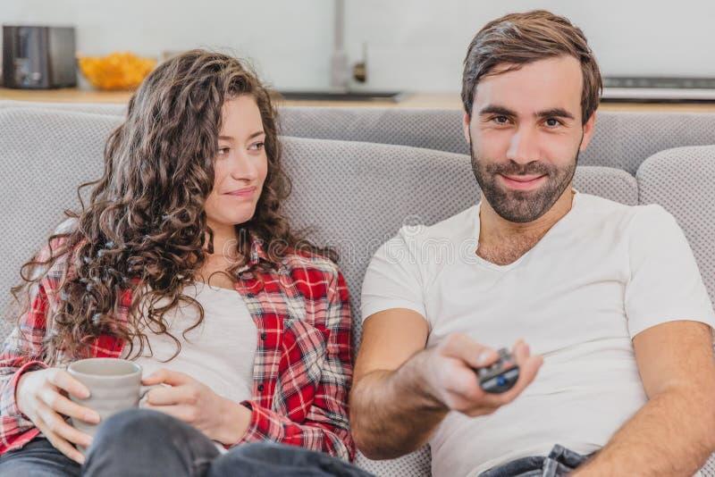 Piękny komicznie młody człowiek trzyma pilota do tv, żony filiżanka kawy Podczas ten mężczyzny spojrzeń przy kamerą i obrazy royalty free