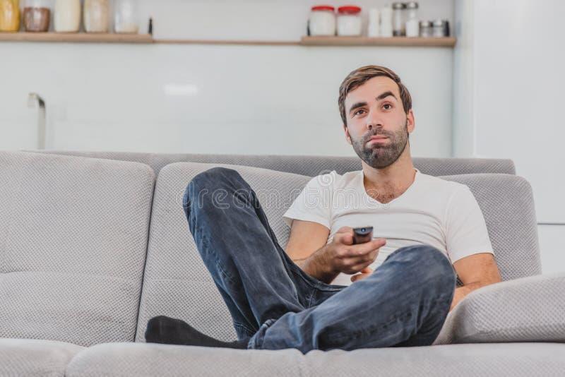 Piękny komicznie młody człowiek trzyma pilota do tv Podczas to TV ogląda podczas gdy siedzący na leżance przy obraz stock