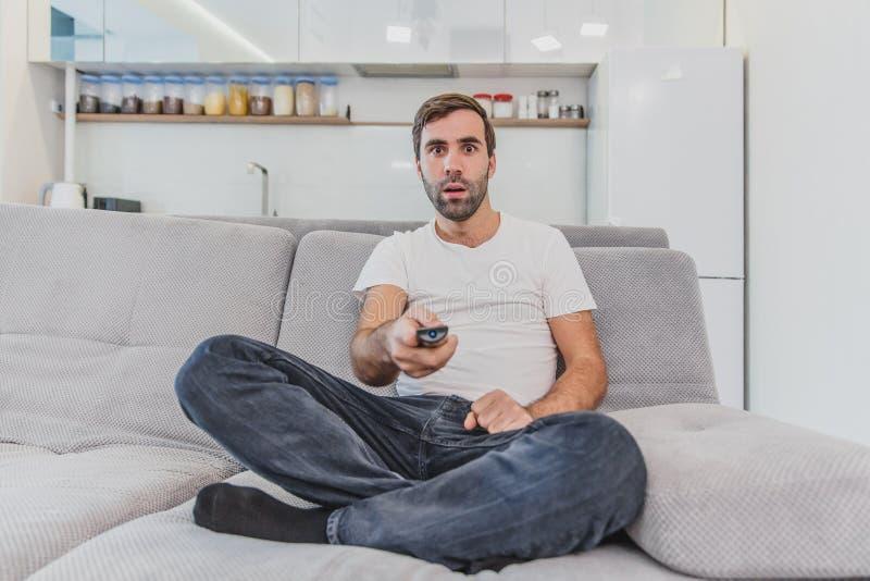 Piękny komicznie młody człowiek trzyma pilota do tv Podczas to TV ogląda podczas gdy siedzący na leżance przy obrazy stock