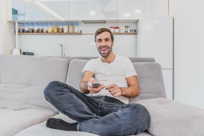 Piękny komicznie młody człowiek trzyma pilota do tv Podczas to TV ogląda podczas gdy siedzący na leżance przy obrazy royalty free