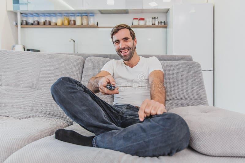 Piękny komicznie młody człowiek trzyma pilota do tv Podczas to TV ogląda podczas gdy siedzący na leżance przy zdjęcia royalty free