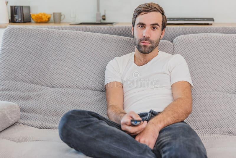 Piękny komicznie młody człowiek trzyma pilota do tv Podczas to TV ogląda podczas gdy siedzący na leżance przy obraz royalty free