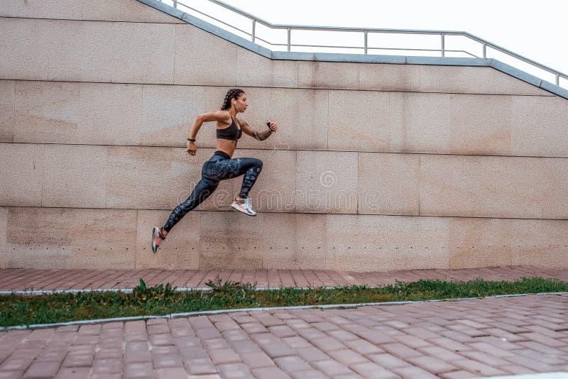 Piękny młoda dziewczyna tatuaży lata miasta bieg skok w ręki smartphone słucha muzykę w hełmofonach, sportswear leggings obraz royalty free
