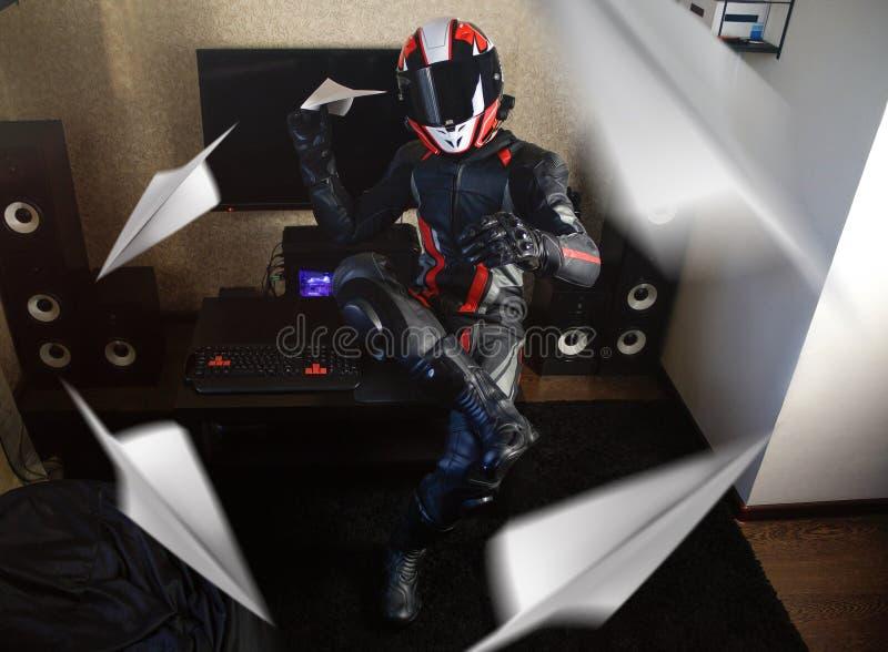Piękny motocyklista w pełnej przekładni i hełmie wszczyna papierowego samolot zdjęcia stock