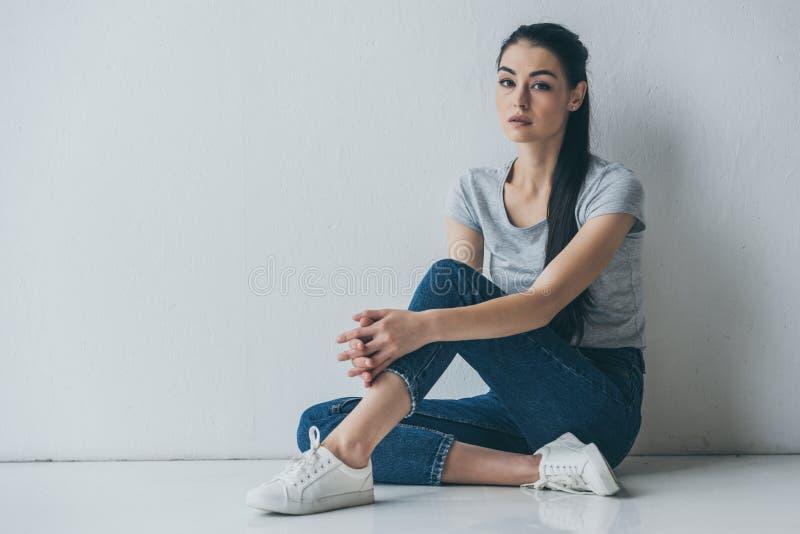 piękny sfrustowany brunetki dziewczyny obsiadanie na podłogowym i przyglądającym zdjęcie stock