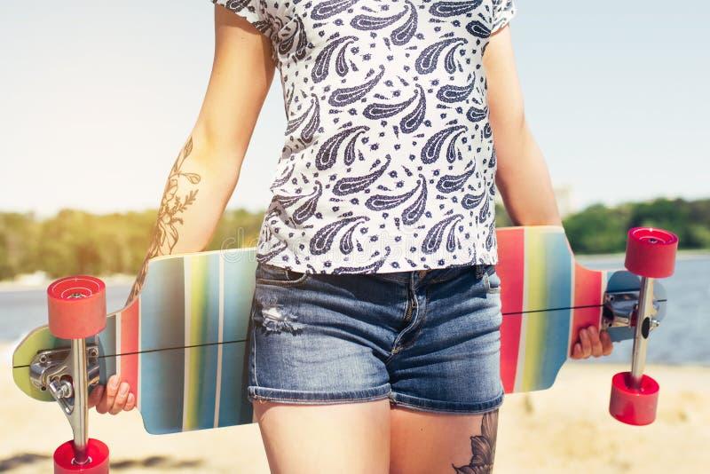 Piękny strzał seksowna młoda dziewczyna chodzi z kolorowym longboard w pogodnej pogodzie w skrótach leisure Zdrowy Styl życia zdjęcie stock