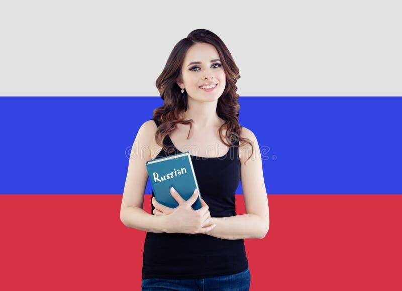 Piękny szczęśliwy kobieta uczeń z podręcznikiem na federacji rosyjskiej flagi tle Uczy się rosyjskiego języka zdjęcie royalty free