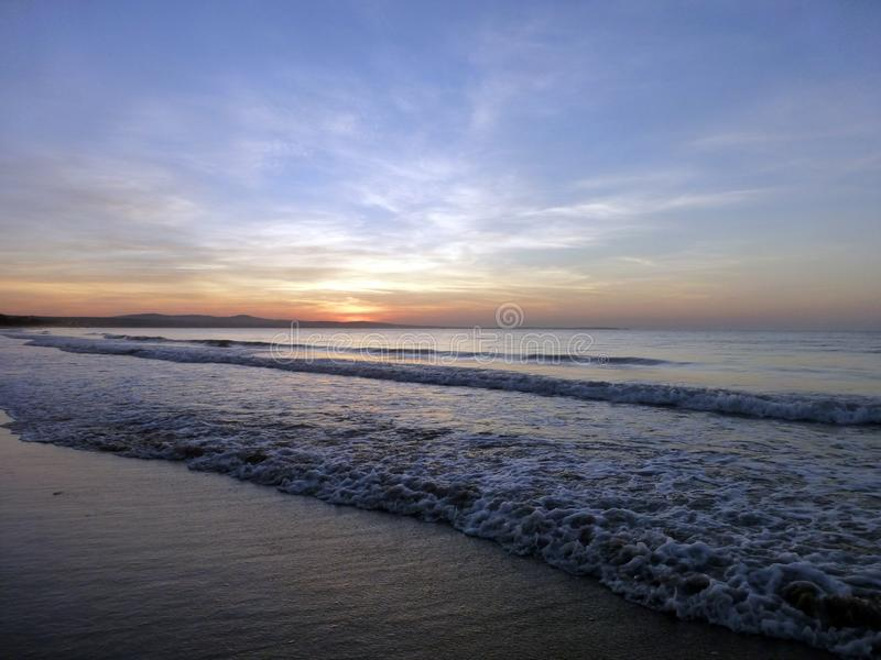 piękny zachód słońca słońce sety w morzu Piaska niebieskie niebo z chmurami i plaża zdjęcia stock