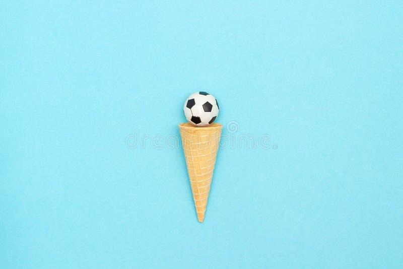 Piłki nożnej lub futbolu piłka w lody gofra rożku na błękitnym tle w minimalnym stylu Pojęcie bawi się rozrywkę Odgórnego widoku  zdjęcia stock