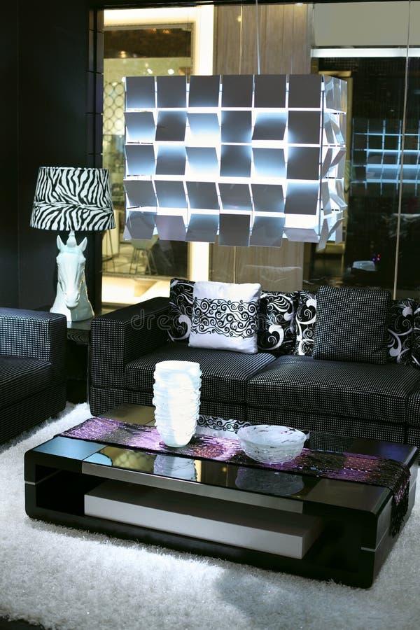 Pièce élégante avec le sofa noir, petite table de revue photo stock