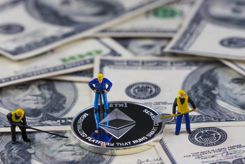 Pièce argentée de creusement d'ethereum de ouvrière miniature de personnes sur cent billets d'un dollar Exploitation virtuelle de images libres de droits