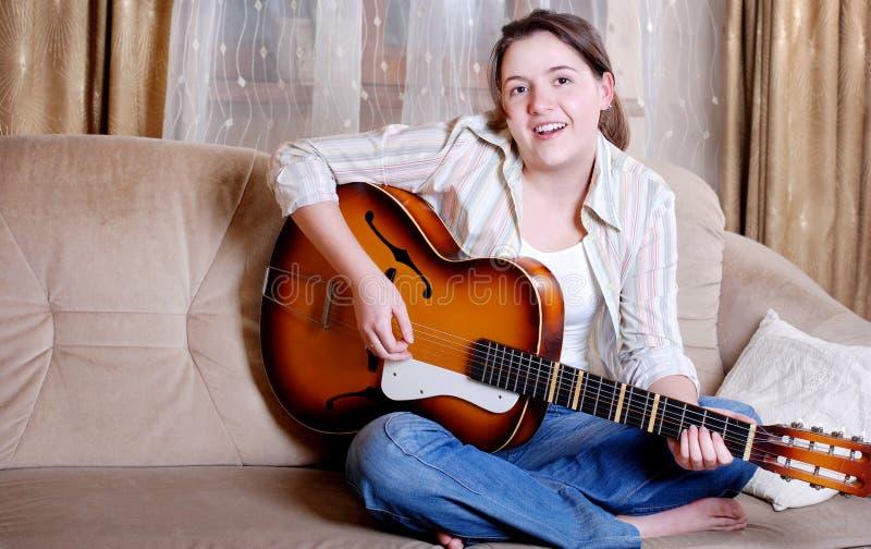 Pièce avec du charme d'adolescente par la guitare photographie stock