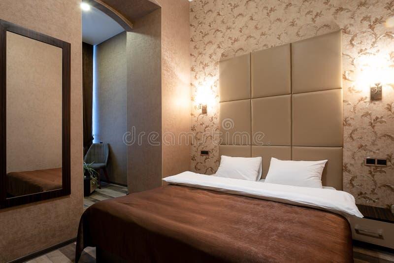 Pièce avec un double lit, la table de chevet, le miroir sur le mur, la porte blanche, les murs beiges, le plancher en stratifié e images libres de droits
