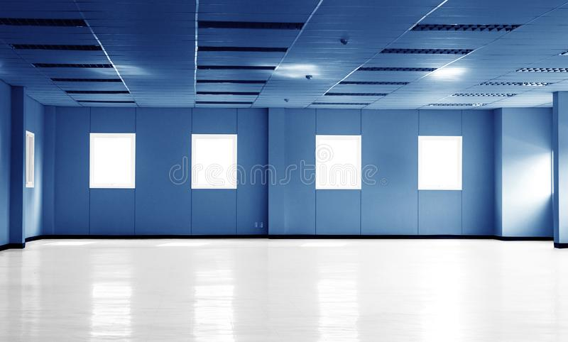 Pièce bleu-foncé vide de bureaux dans l'immeuble de bureaux ou usine avec les fenêtres et l'espace de copie photographie stock