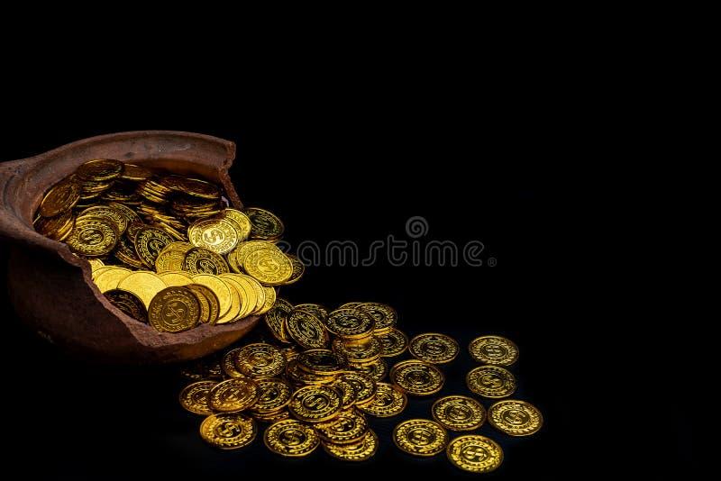Pièce d'or dans la main de dame sur des sorts empilant les pièces de monnaie d'or à l'arrière-plan blanc de pot cassé image stock