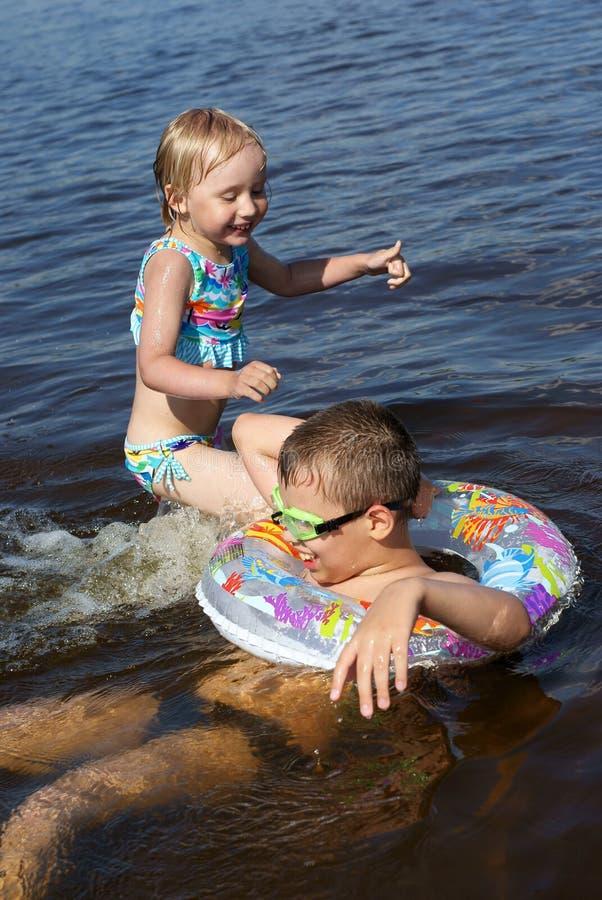 Pièce d'enfants dans l'eau photos stock
