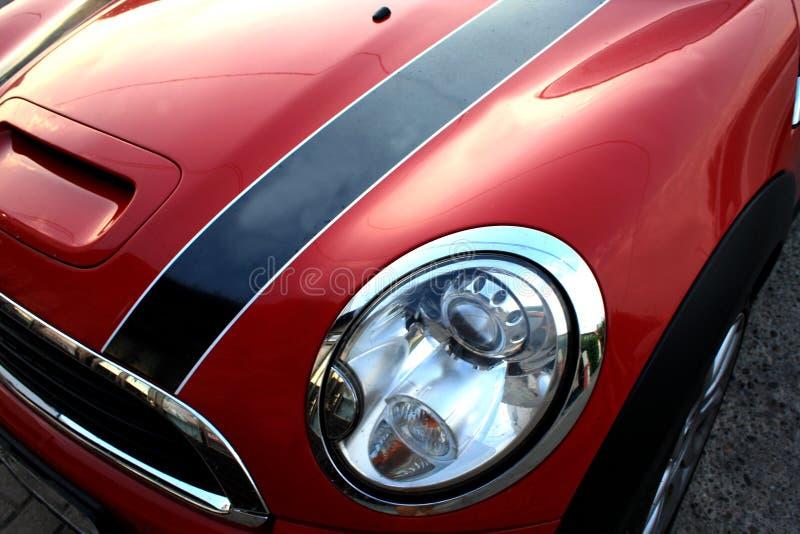 Pièce d'isolement automobile de sport rouge et petit avec le phare et la lueur photographie stock
