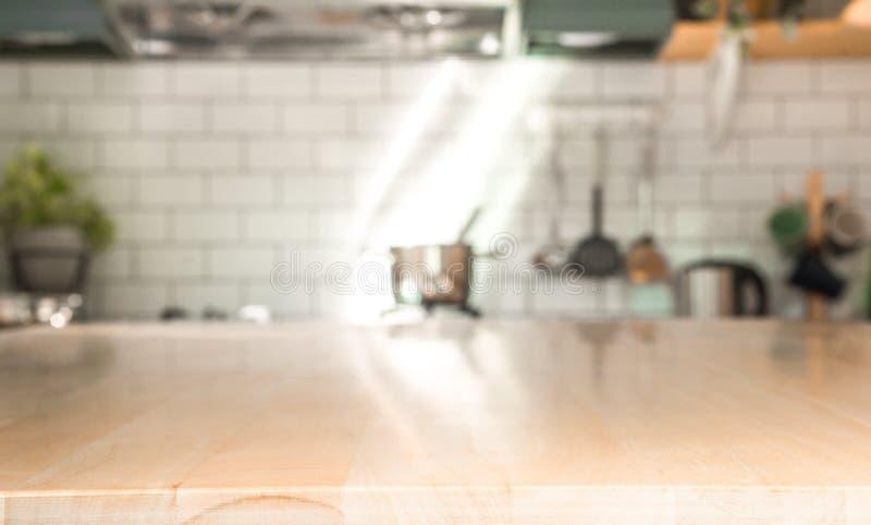 Pièce de cuisine et concept de fond - table en bois brun clair brouillée avec le beau fond moderne de pièce de cuisine de cru et image stock
